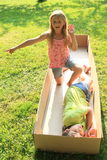 Children playing and sleeping in a box. Barefoot children - boy sleeping and girl smiling and playing in a paper box Stock Photography