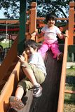 Children playing slide. Happy children playing slide at the playground in the park on sunny day Royalty Free Stock Photo