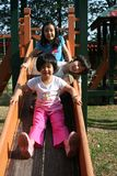 Children playing slide. Happy children playing slide at the playground in the park on sunny day Royalty Free Stock Photos