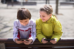 Children playing on smartphones on  bench Royalty Free Stock Image