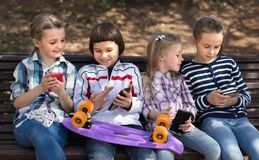 Children playing in smartphones on street bench in park Stock Images