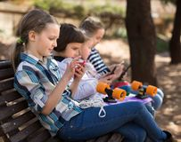 Children playing in smartphones on street bench in park Royalty Free Stock Photography