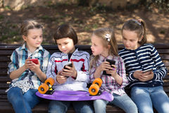 Children playing in smartphones on street bench in park Stock Photography