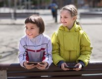Children playing on smartphones on the street bench Stock Photo