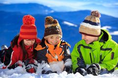 Children playing in snow. Three children playing in winter snow with mountains in the background Royalty Free Stock Photos