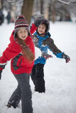 Children playing with snow. Two children at snowy park throwing  snowballs Royalty Free Stock Photo