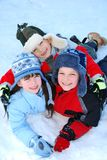 Children playing in snow. An overhead view of three siblings playing happily in the snow on a winter day Stock Photos
