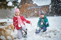 Children playing on snow with dog in winter holiday Stock Photography