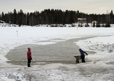 Children are playing with snow at frozen river in Rovaniemi, Finland Stock Photos