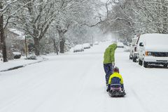Children playing in the snow with a sled. Children walk down the center of an empty street dragging sleds in the freshly fallen winter snow Stock Photos
