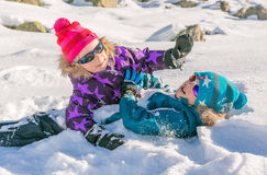 Children playing in the snow. Children wearing colorful clothes playing in the snow on a sunny day Stock Image