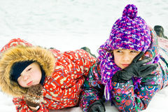 Children playing on snow in winter time Royalty Free Stock Images