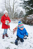 Children playing in snow in winter Royalty Free Stock Images