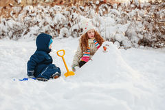Children playing with a snowman on a winter walk in the park. Stock Photo