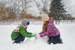 Children playing with a snowman on a winter walk in the park. stock images