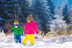Children playing in snowy winter park Royalty Free Stock Image