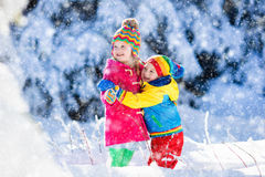 Children playing in snowy winter park Stock Photo