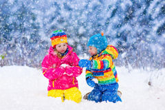 Children playing in snowy winter park Stock Images