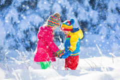 Children playing in snowy winter park Royalty Free Stock Photography