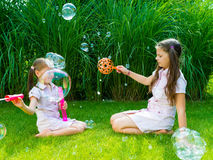 Children playing with soap bubble wand in the park on a sunny su Stock Photos