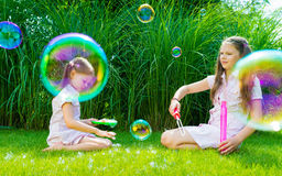 Children playing with soap bubble wand in the park on a sunny summer day royalty free stock photography