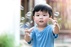 Children playing with soap bubbles. Royalty Free Stock Image
