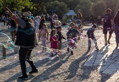 Children playing with soap bubles in the light of sunset royalty free stock image