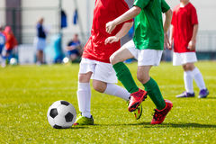 Children Playing Soccer Football Match. Football soccer game. Players footballers running and playing football match Stock Photo