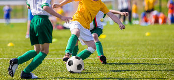 Children playing soccer football match. Young boys of football academy playing football soccer game. Running players in colorful uniforms Stock Images