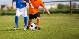 Children playing soccer football match. Young boys playing football soccer game. Running players in blue and orange uniforms Royalty Free Stock Photo