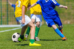Children Playing Soccer Football Match. Young boys playing football soccer game. Running players in blue and yellow uniform. Final game of football tournament Royalty Free Stock Photo