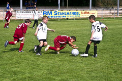 Children playing soccer in an outdoor grass arena Royalty Free Stock Photo