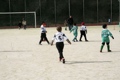 Children playing soccer in winter Royalty Free Stock Photography