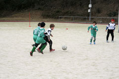 Children playing soccer in winter Stock Images