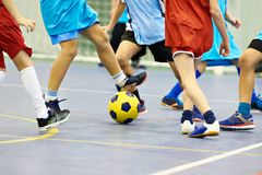 Children playing soccer indoors. Children playing soccer with yellow football indoors royalty free stock photos