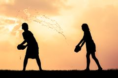 Children playing splash water Songkran silhouette. Children playing splash water on Songkran silhouette royalty free stock photography