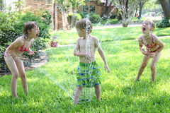 Children Playing in Sprinkler. Three little children play in the water sprinkler in the summer Stock Photo