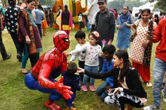 Children playing with a statue of Spiderman. Chandigarh, India – Feb 19, 2017: Children playing with a statue of Spiderman at Rose Festival in Zakir Hussain Royalty Free Stock Image
