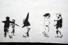 Children Playing Stencil Art. A photograph of a public wall with stencils of children playing in black Stock Image