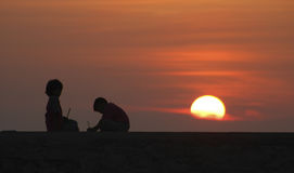 Children Playing At Sunset. Two young children playing silhouetted against an orange sunset with large sun suspended in clouds Stock Image