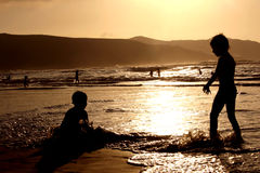 Children Playing on Sunset Beach. Two bouys in the waterat sunset Royalty Free Stock Photos