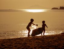 Children playing on the sunset beach. Silhouettes of two children playing on the beach Stock Photography