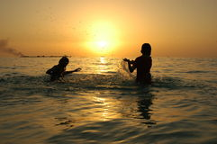 Children playing when sunsets. Children playing in the sea. when sun goes down Royalty Free Stock Image