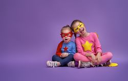 Children are playing superhero. Little children are playing superhero. Kids on the background of bright ultra violet wall. Girl power concept. Yellow, pink, blue Stock Photography