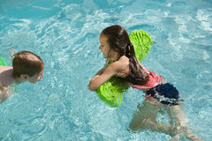 Children Playing In Swimming Pool. Happy children playing with float toys in swimming pool royalty free stock photos