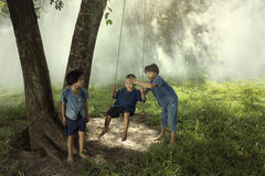 Children playing swing. Group of children playing swing under tree Stock Photos