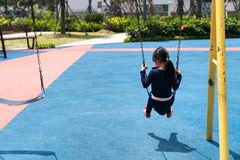 Children playing swing on playground. Kids play outdoor on sunny day.  Royalty Free Stock Images