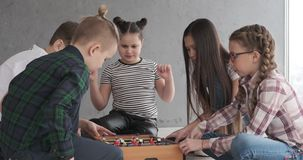 Children playing table soccer at home. Boys and girls playing table soccer at home stock footage