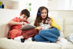 Children Playing With Tablet And MP3. Children Playing With Digital Tablet And MP3 Player Stock Photo