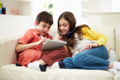 Children Playing With Tablet And MP3 Royalty Free Stock Images